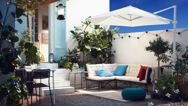 An outdoor patio with a modular sofa with white cushions, a white parasol, a blue-green pouffe and plenty of plants.