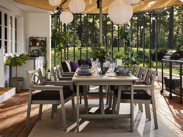 An outdoor patio with the grey BONDHOLMEN dining set, a large outdoor umbrella, LED lighting and outdoor storage in the background.