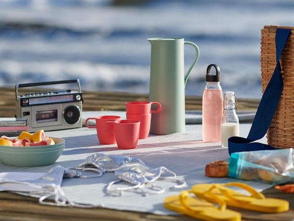 An outdoor place setting with pink cups, a light green carafe, yellow flip flops and a portable radio.