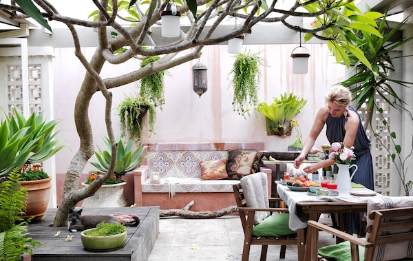 An outdoor scene with dining table, tiled bench and various plants.