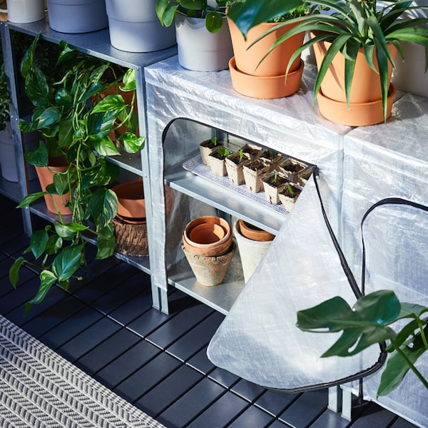 An outdoor setting with the HYLLIS shelf unit and cover filled with plant and plant pots.
