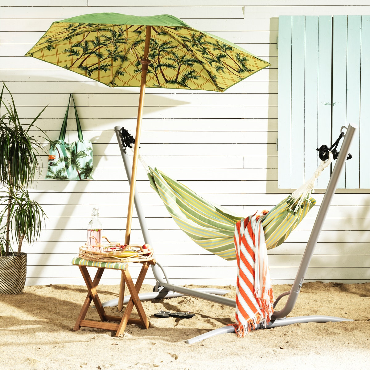An outdoor space on the beach with the SOLBLEKT collection umbrella, stool and hammock set up.