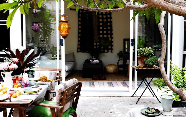 An outdoor space with dining table and chairs with food and drink.