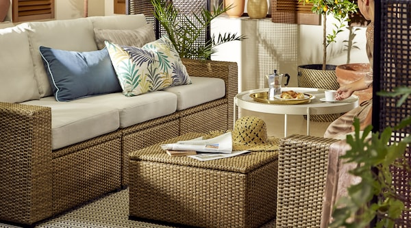 An outdoor space with light brown SOLLERON lounge furniture with tan cushions and an ottoman and table holding newspapers, coffee and breakfast.