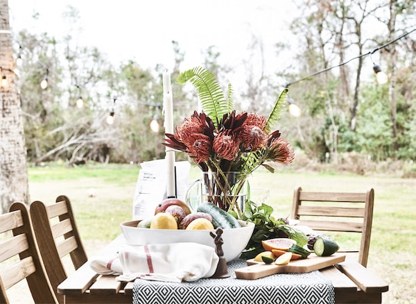 An outdoor table set with flowers and fresh produce.