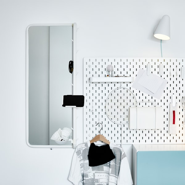 An outfit corner with a white pegboard, a white wall lamp and a white mirror with a phone holder.