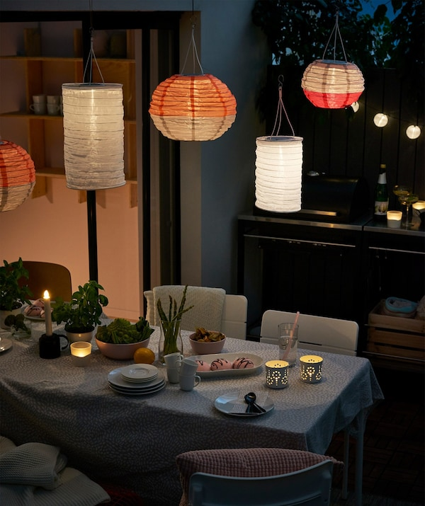 An outside dining area illuminated with IKEA SOLVINDEN solar-powered pendant lamps.