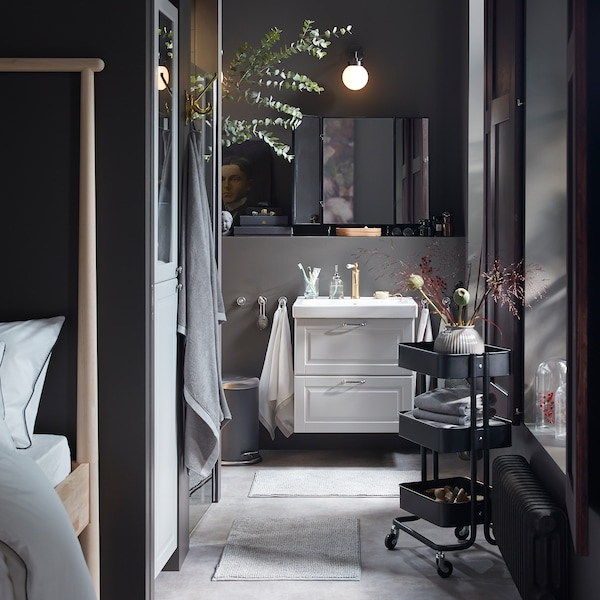 An overall grey bathroom with a wash stand and high cabinet in light grey, a black trolley and many dried decorative flowers.