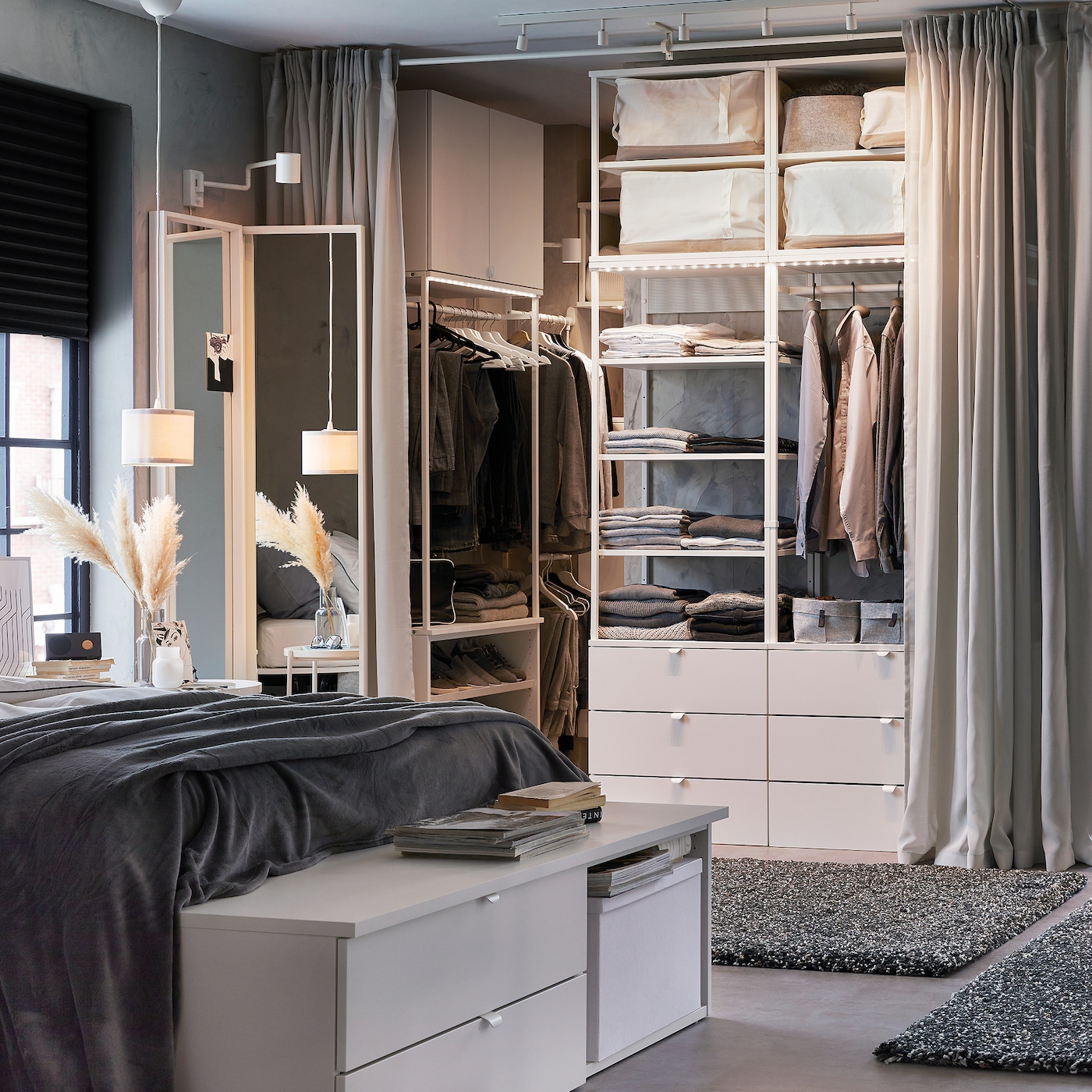 An overall white and grey bedroom with a white bench with drawers, an open wardrobe, light grey curtains and dark grey rugs.