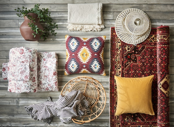 An overhead image of bedroom textiles in red and yellow tones including the SPRÄNGÖRT quilt cover and two pillowcases with pink floral prints.