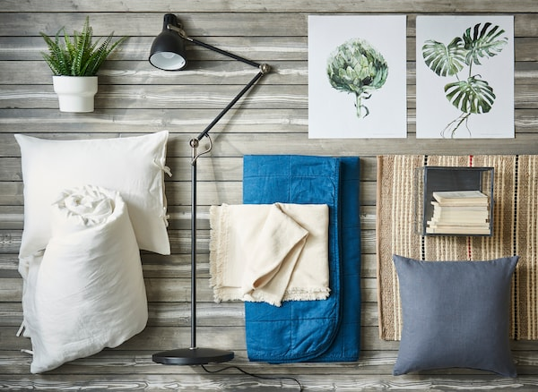 An overhead image of bedroom textiles in whites and blues with plants and prints of plants