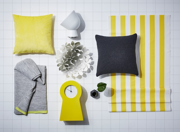 An overhead mood board featuring products with yellow accents, such as IKEA SOMMAR 2018 yellow cushion cover.