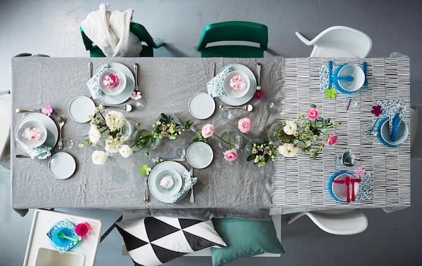 An overhead shot of a dining table set for a family lunch with a grey tablecloth.