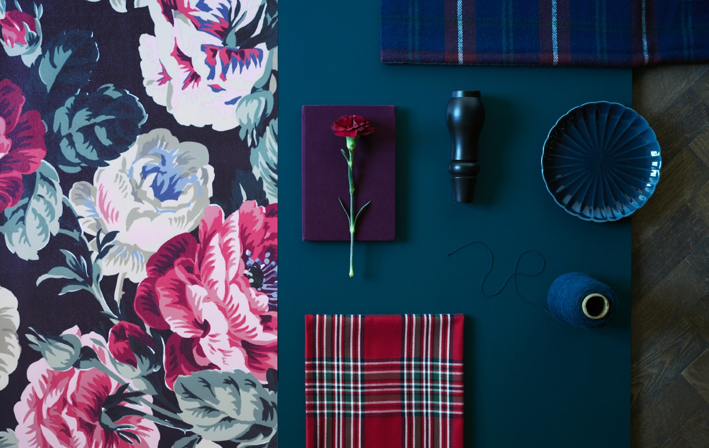 An overhead view of a bold floral textile, plaid textiles, and other decoration arranged on a wooden floor.