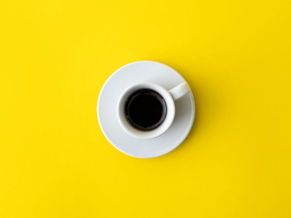An overhead view of a cup of black coffee in a porcelain white mug.