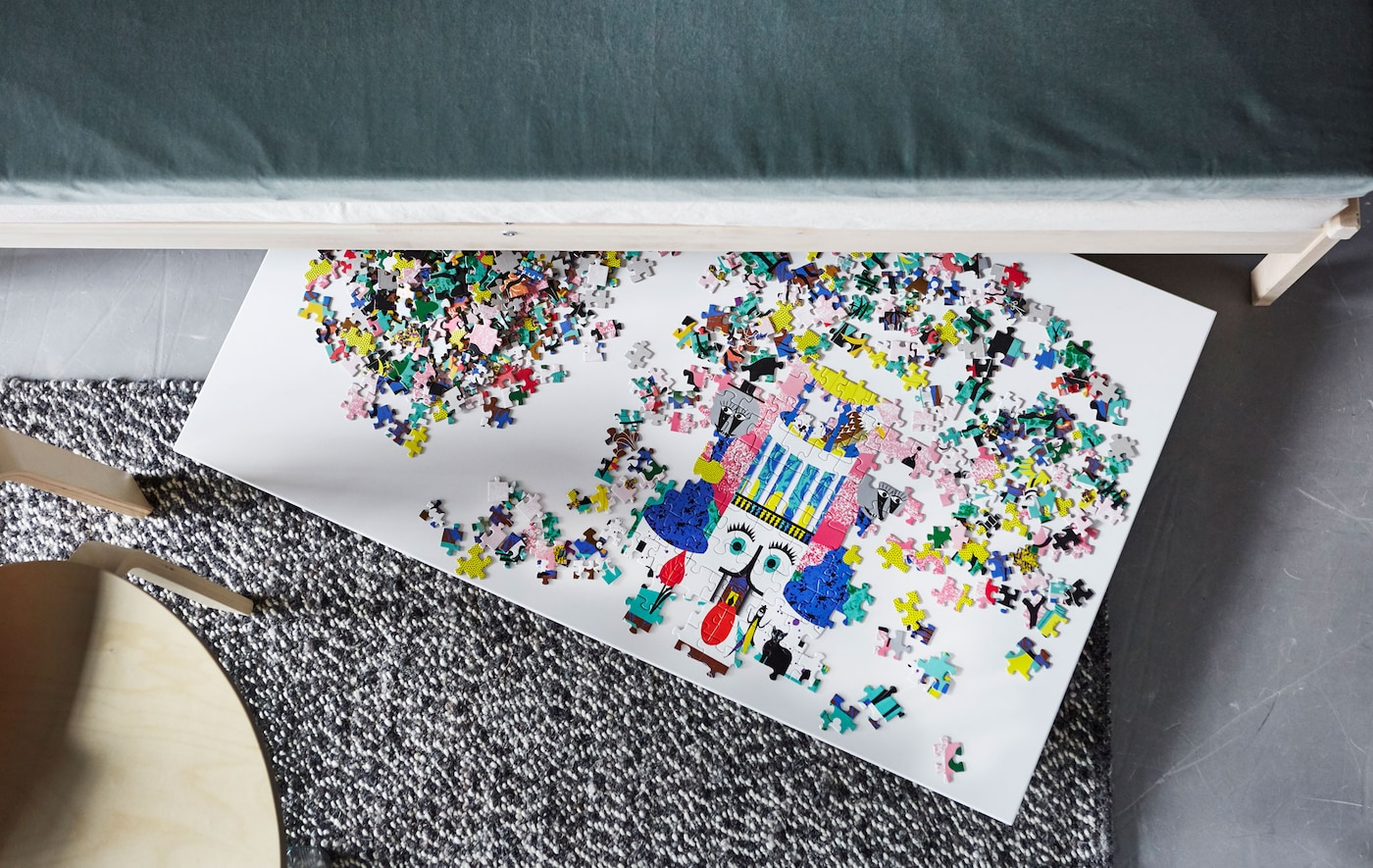 An overhead view of a puzzle on a board that's sticking out from under a sofa.