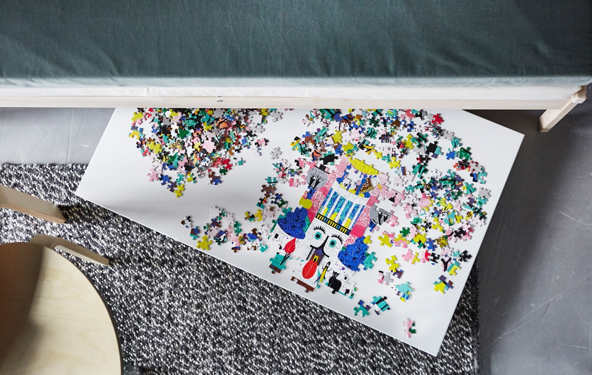 An overhead view of a puzzle on a board that's sticking out from under a sofa