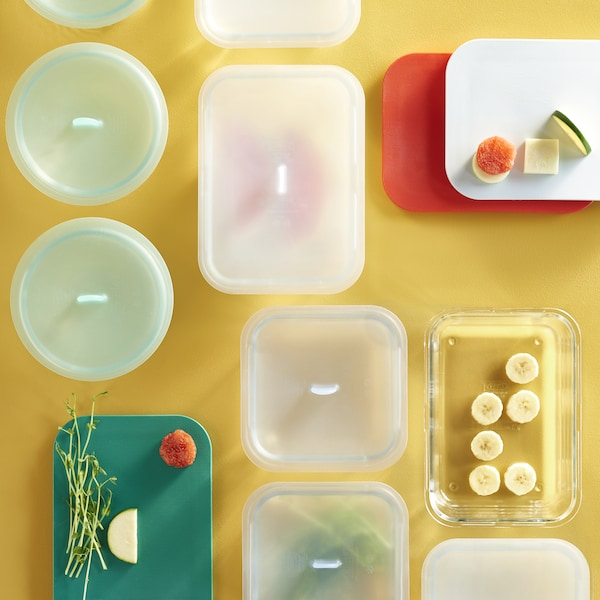 An overhead view of IKEA glass food storage boxes of different shapes and sizes with plastic lids.