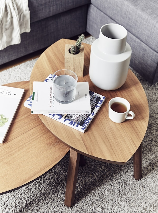 An overhead view of two leaf-shaped coffee tables with a white vase, candle, and mug of coffee.