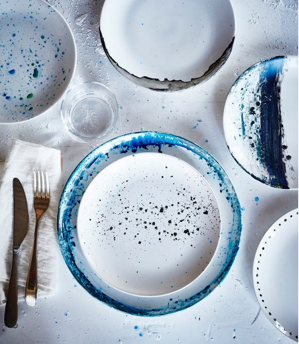 An overhead view on of white IKEA FÄRGRIK plates that have been painted with different designs in shades of blue.