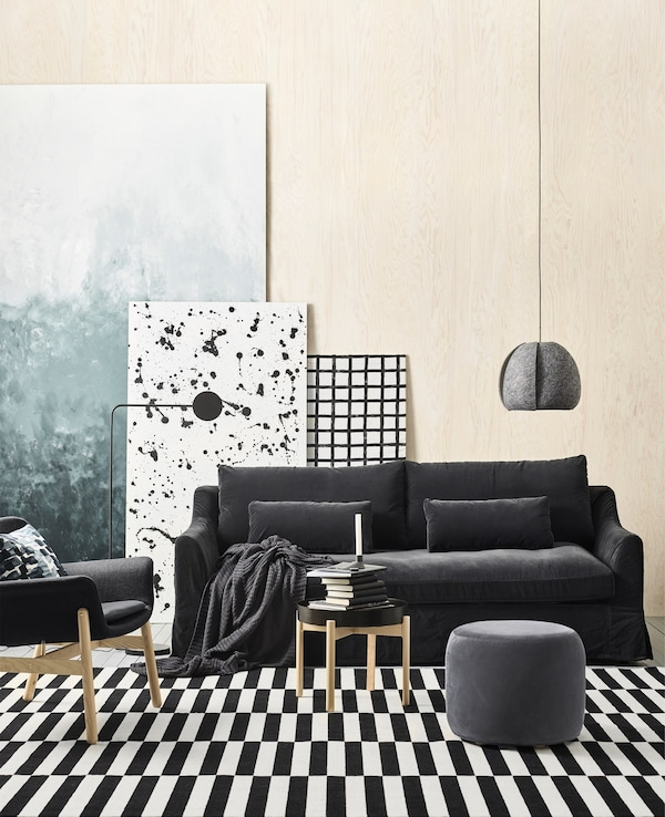 An overview of a Scandinavian living room, including pine walls, black velvet sofa and a black and white striped rug.