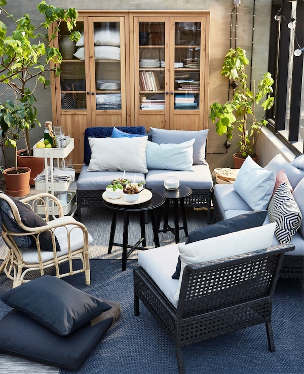 An overview of an outdoor living room setting including black furniture with blue and beige cushoins.