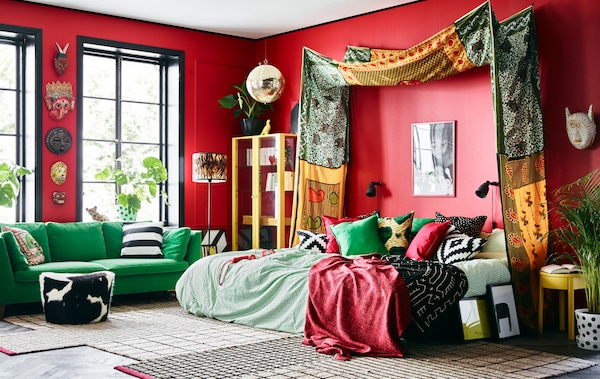 An overview of Cecilia's bold dream bedroom with bright African patterned textiles, colourful green furniture and red walls.