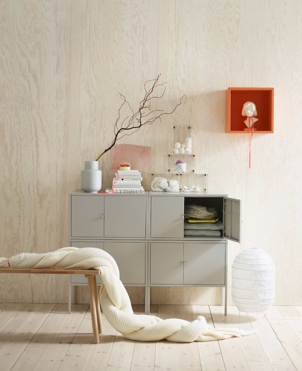 An overview of classic Scandinavian elements, including a soft blanket, pine walls and a pop of orange with an EKET cabinet.
