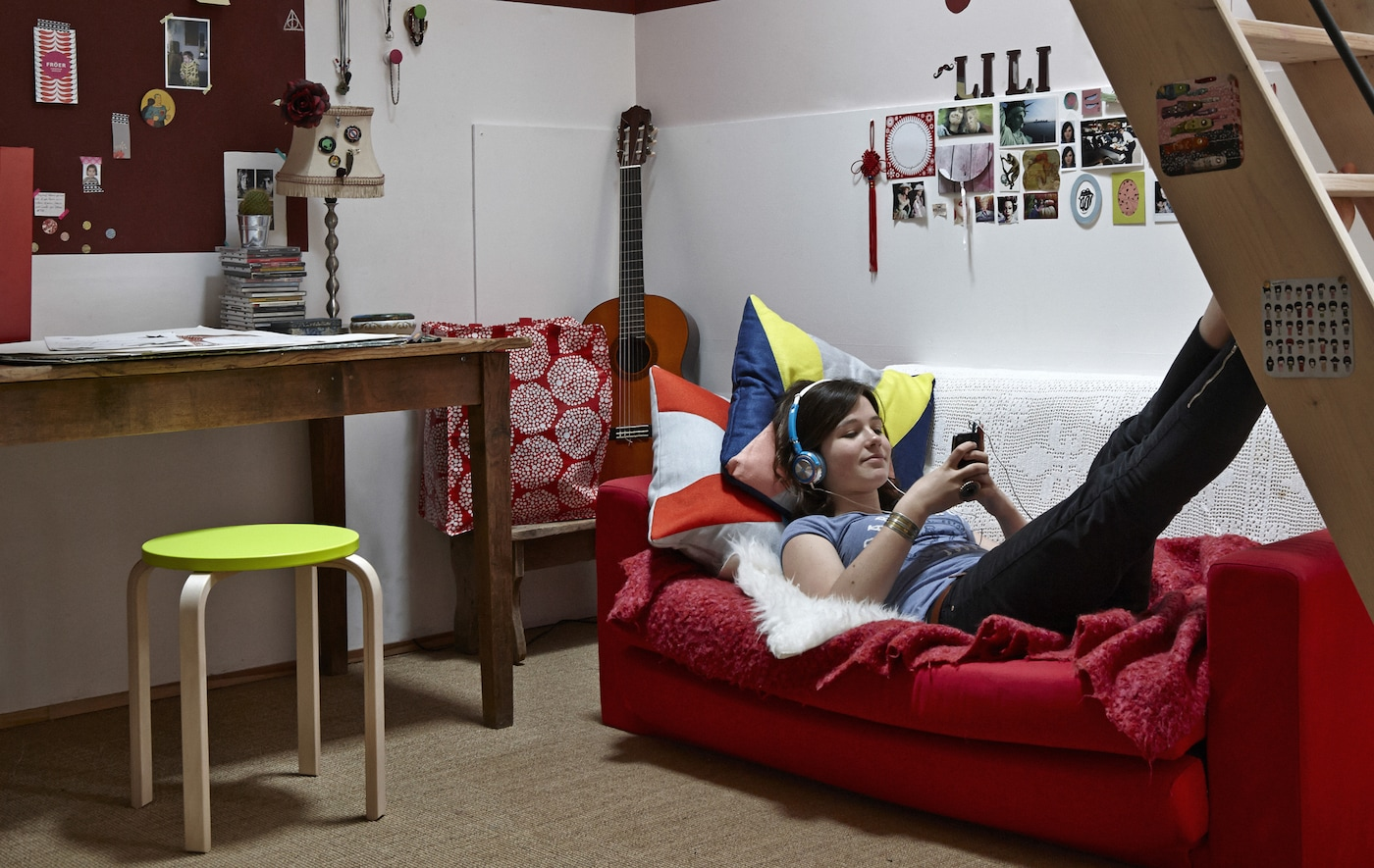 An overview of French teenager Lison's teen bedroom, including a red two-seater sofa and personalised lime green stool.