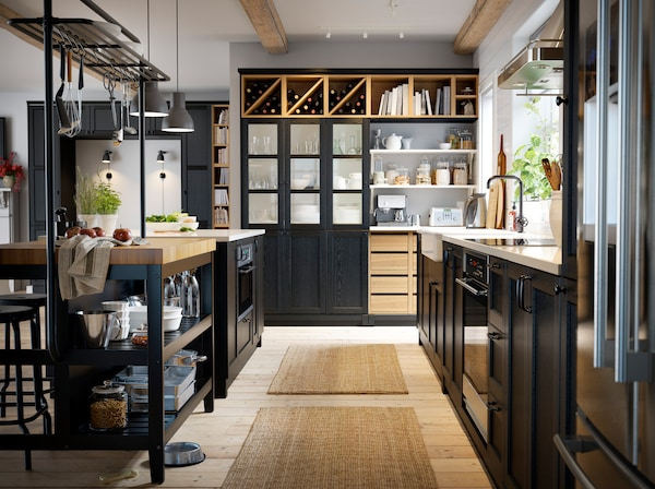 An overview of the IKEA VADHOLMA kitchen island, light wood open storage shelves and LERHYTTAN black front cabinet doors.