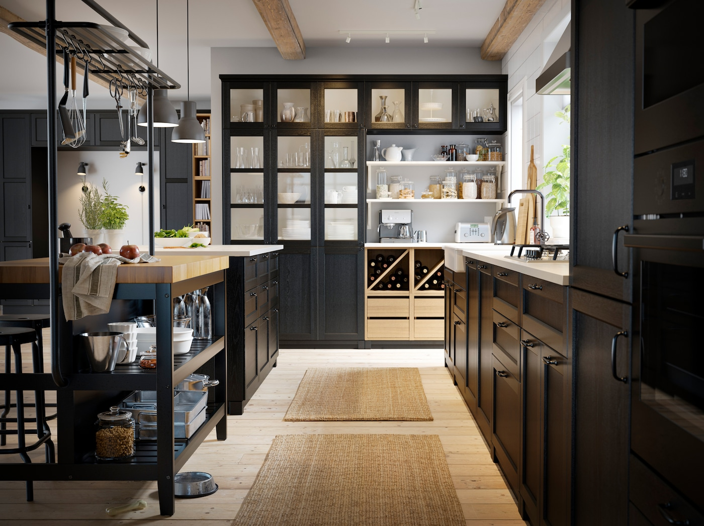 An overview of the IKEA VADHOLMA kitchen island, light wood open storage shelves and LERHYTTAN black front kitchen cabinet doors.