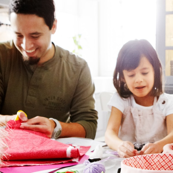 An parent and his child are doing crafts together, one of the themes of the IKEA Let's Play campaign.