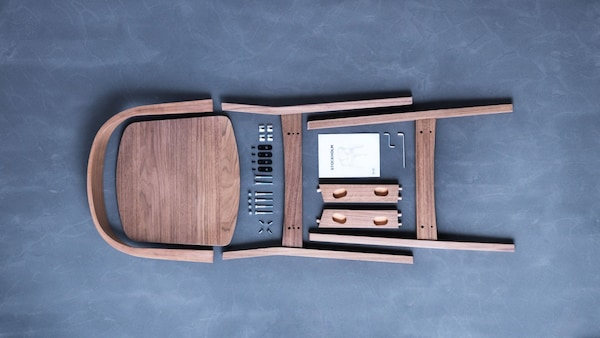 an unassembled wood chair with hardware