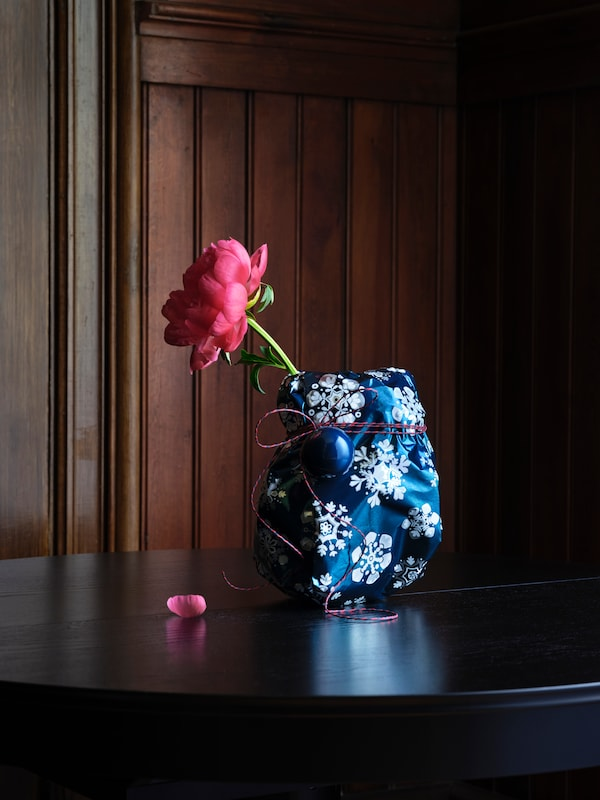 An unknown IKEA Vase is wrapped in festive paper with a cut flower poking out the top