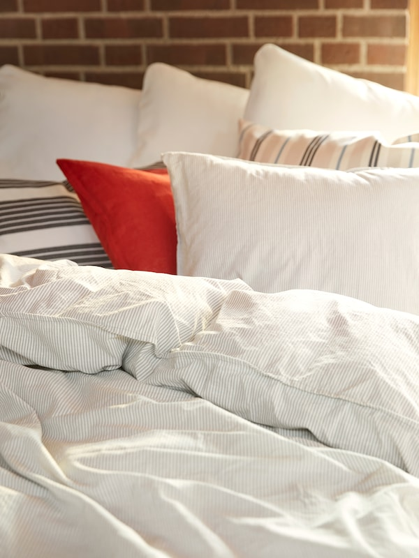 An unmade bed against a brick wall, dressed in a cream-coloured and striped BERGPALM quilt and pillowcases.