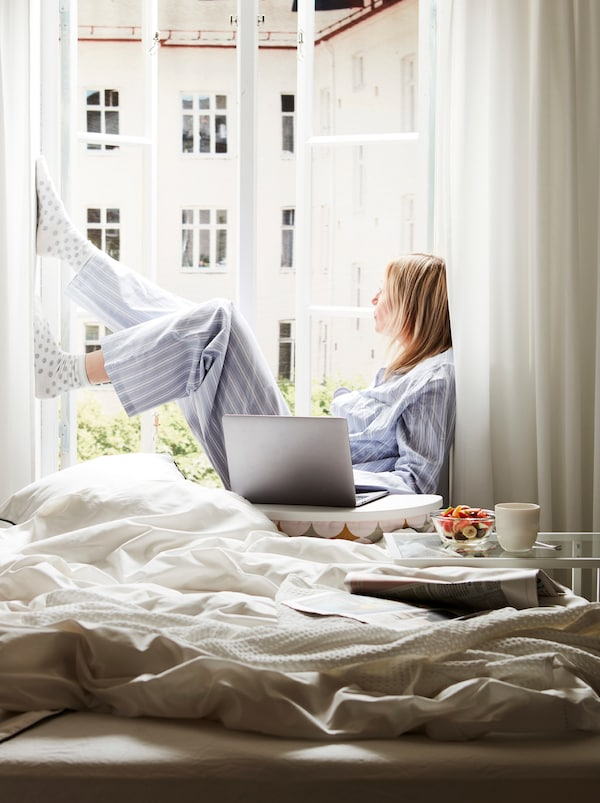 An unmade bed next to an open, sunlit window. On the sill sits a woman, a computer on a BYLLAN laptop support beside her.