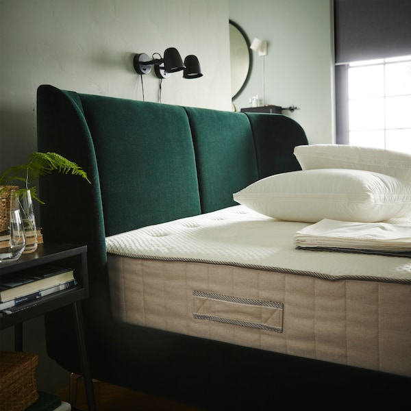 An upholstered bed in green velvet, a white/beige mattress, two white pillows, folded bed linen and two black wall lamps.