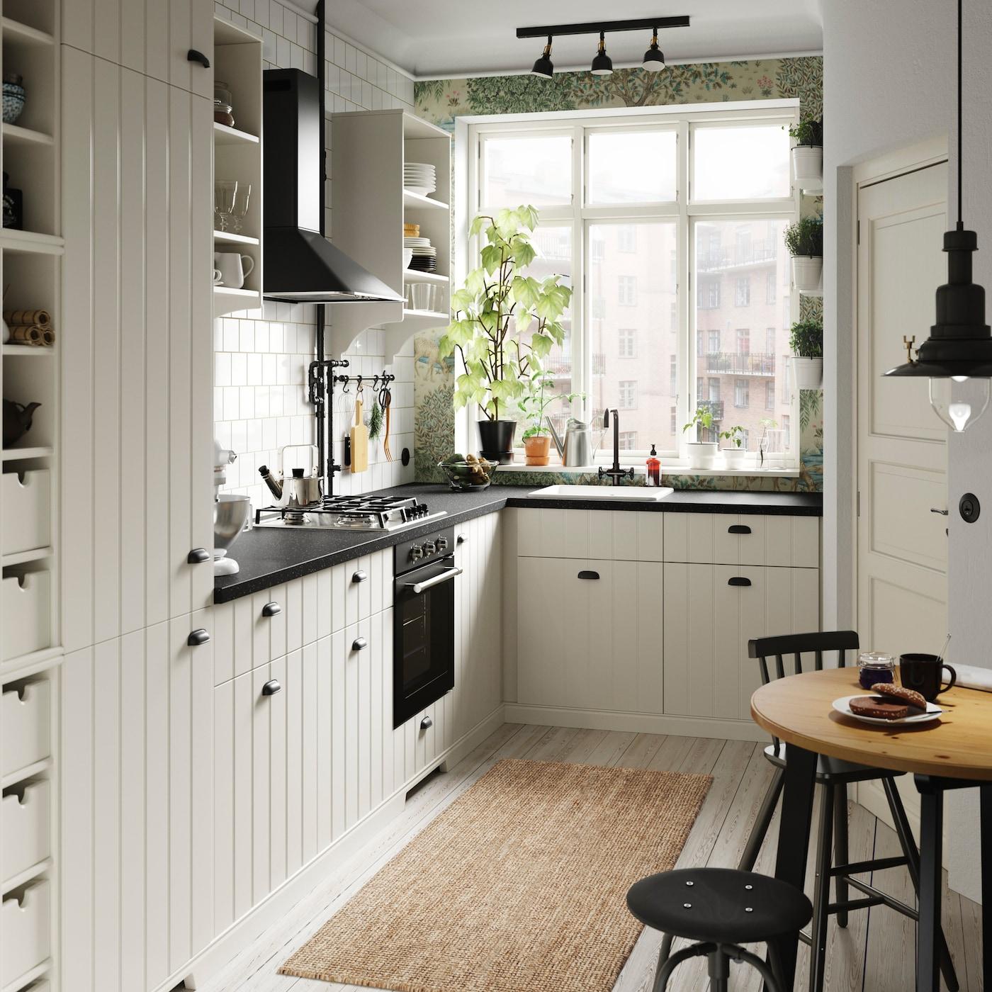 Anche se lo spazio è poco, puoi creare una cucina accogliente dallo stile country con le ante METOD HITTARP bianche, scanalate verticalmente, e i mobili a giorno e i portabottiglie TORNVIKEN color bianco sporco – IKEA