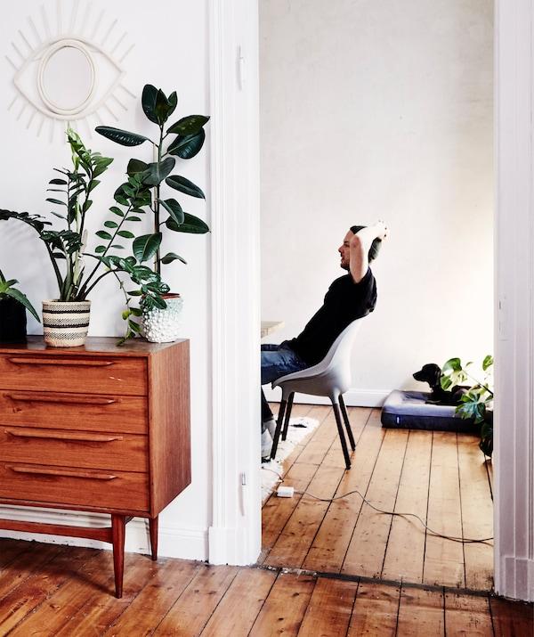 André siedzi na krześle widocznym przez drzwi, stojącym na drewnianych deskach podłogowych w otoczeniu mebli w stylu vintage.