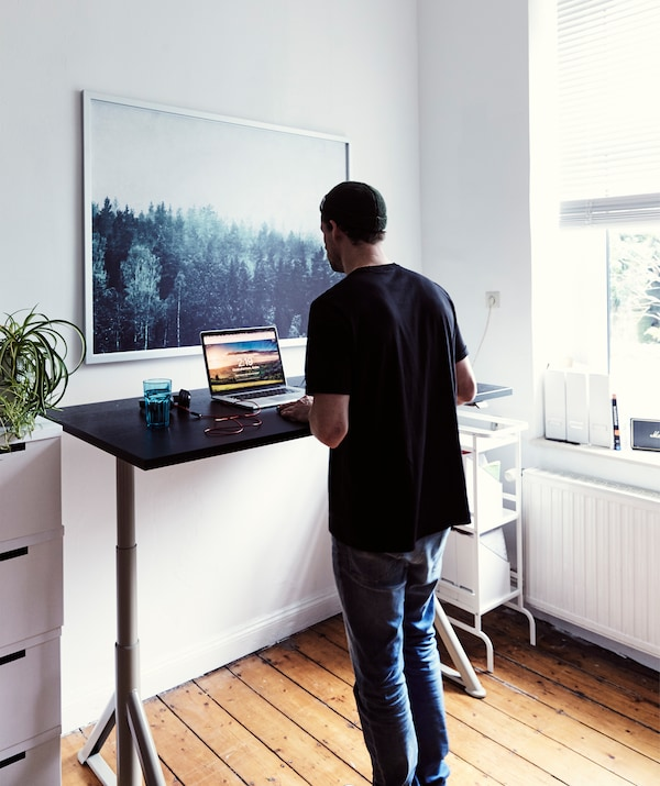 André working at a standing desk in a white room with a large picture of a forest on the wall.