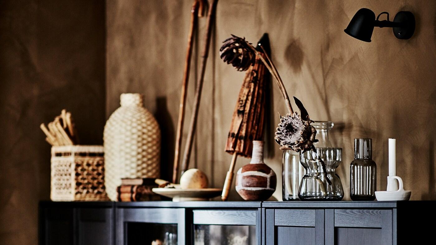 Angolo di soggiorno con mobili HAVSTA scuri e tanti oggetti d'arte, all'interno e sul piano superiore, realizzati in materiali naturali.