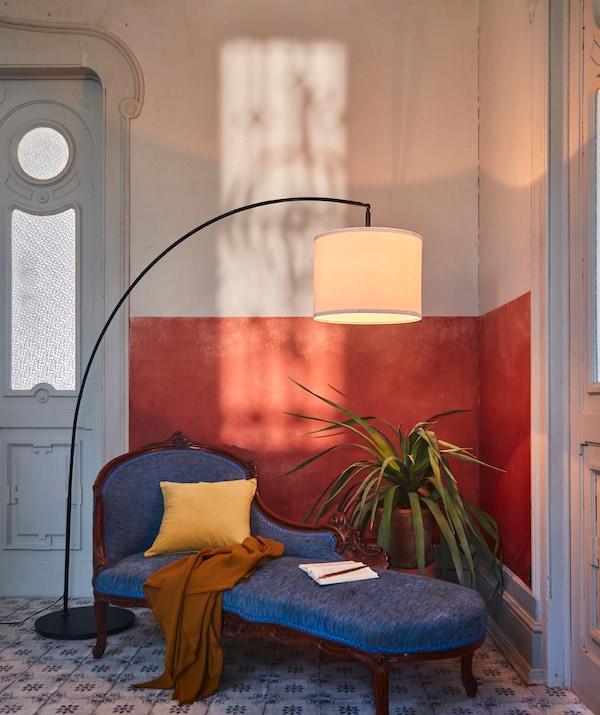 Angolo di una stanza decorato con materiali e dettagli raffinati. Lampada da terra SKAFTET ad arco sopra a una pianta e a una elegante chaise longue - IKEA
