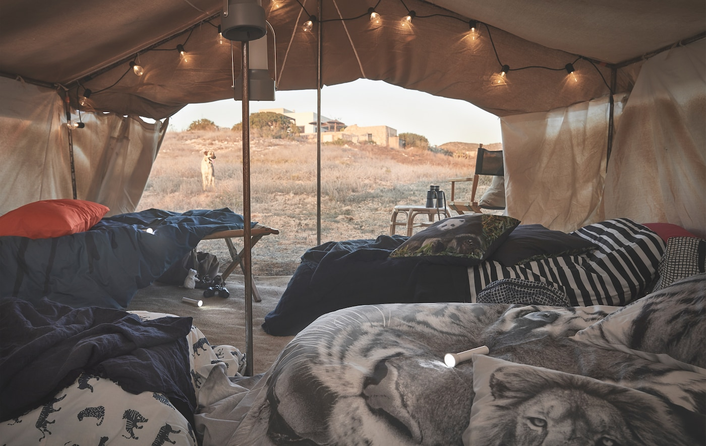 Animal-print bedding on beds under a canvas in the desert.