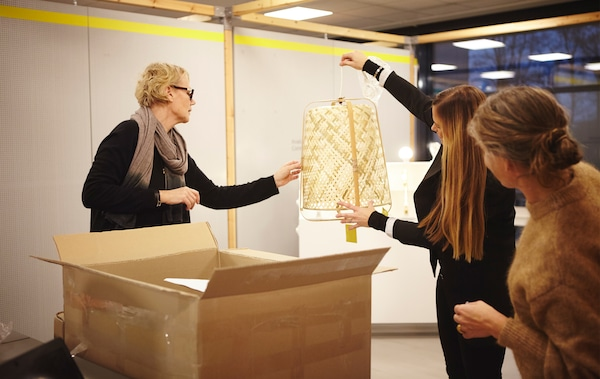 Anna Granath holds up a woven lamp above a large box while two other people look at it.