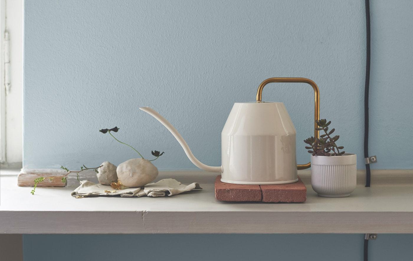 Annaffiatoio bianco con manico color oro, su una mensola con un vaso e alcune pietre - IKEA