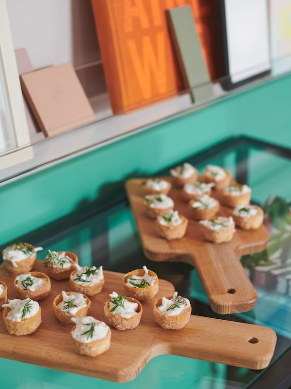 Antipasti serviti su due taglieri PROPPMÄTT fatti con le basi per salatini KRUSTADER, su un tavolo in vetro - IKEA