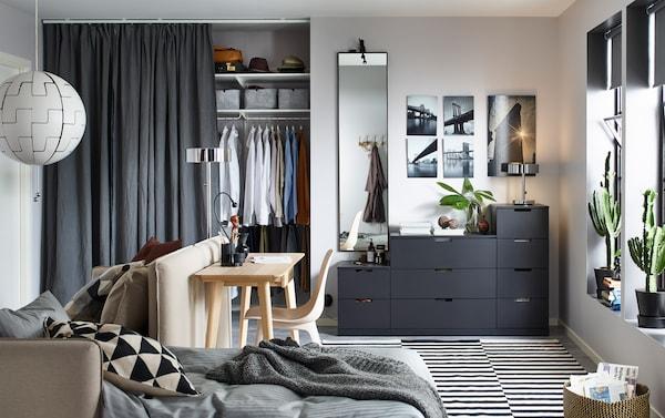 Antraciete NORDLI ladekast met 9 lades in een kleine woonkamer met een slaapbank en een bureau