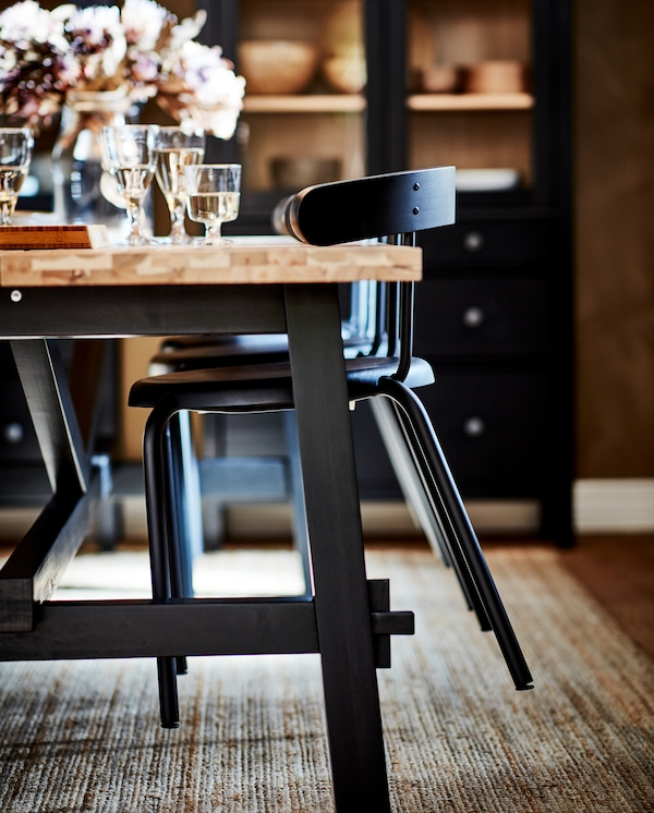 Antrasiitin väriset tuolit on nostettu pöydälle helpottamaan pöydän alla olevan juuttimaton puhdistamista.
