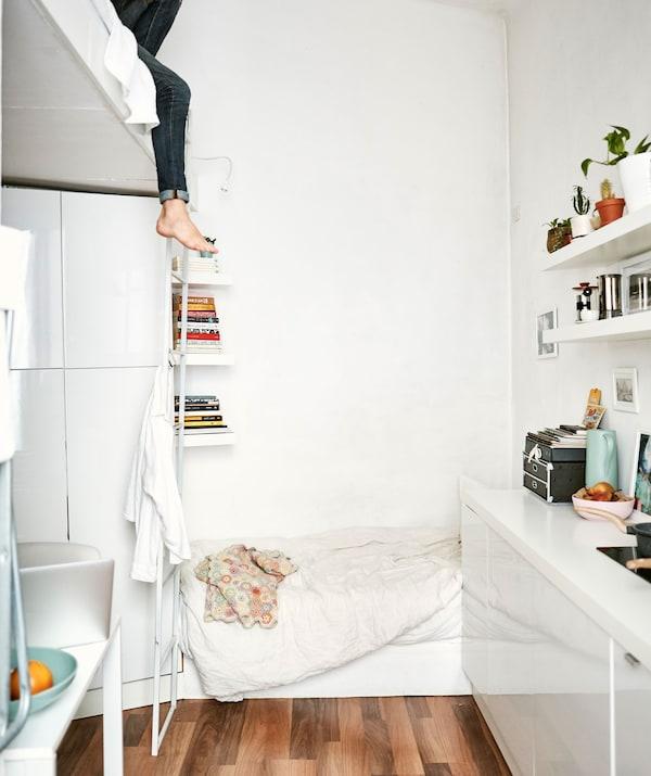 Apartament mic, alb complet, cu un pat de zi la mezanin și un perete cu spațiu de bucătărie.