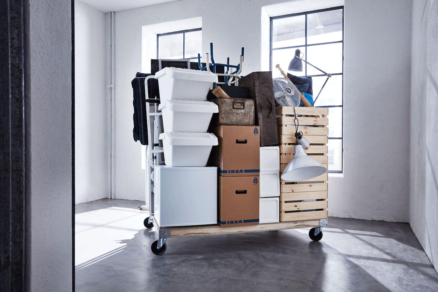 Appartement emballé et déplacé dans des boîtes, sur un chariot.